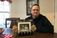 "Keith Michael holds a photo on Friday, Nov. 13, 2020, in Jonesboro, Ark., of him and his wife, Susanne, a fourth-grade teacher who died from coronavirus. ""She just basically would eat, sleep and drink teaching. She loved it,"" said her husband. (AP Photo/Adrian Sainz)"