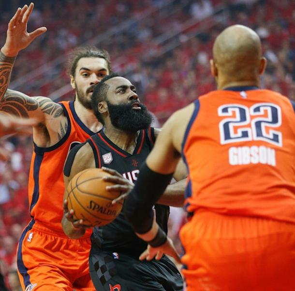 James Harden (C) of the Houston Rockets drives to the basket past the Oklahoma City Thunder players during the 2017 NBA playoffs' first round, in Houston, Texas, on April 16, 2017