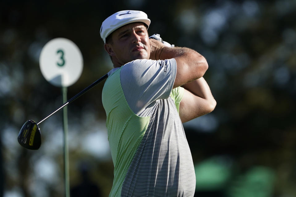 Bryson DeChambeau watches his second tee shot on the third hole after his first ball was lost during the second round of the Masters golf tournament Friday, Nov. 13, 2020, in Augusta, Ga. (AP Photo/David J. Phillip)