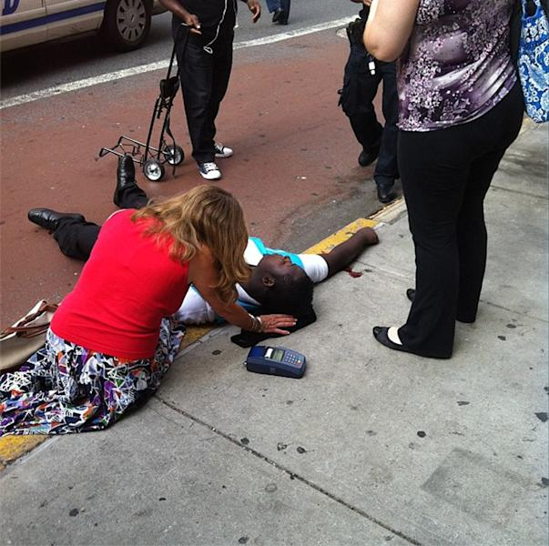 """ADDS NAME OF VICTIM AND HIS CONDITION - This photo posted to an Instagram account belonging to a person identified as mr_mookie, an eyewitness at the scene, shows shooting victim Robert Asika being tended to by pedestrians outside the Empire State Building in New York, Friday, Aug. 24, 2012, after a laid-off worker fatally shot an executive at his former company. Asika, who was shot in the right arm, said he was """"100 percent positive"""" that a police officer had shot him. He also said he saw the suspect fire his gun at the officers. (AP Photo/mr_mookie via Instagram)"""