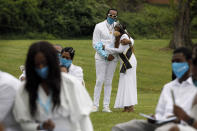 """Iran """"Bang"""" Paylor, of Washington, left, is comforted by his friend Jewel Parker, during a socially distanced outdoor memorial service for his mother, Joanne Paylor, 62, of southwest Washington, at Cedar Hill Cemetery in Suitland-Silver Hill, Md., Sunday, May 3, 2020. The original funeral for Paylor, who the family believes died of a heart attack, was delayed for close to two months while her family hoped social distancing guidelines would be lifted. Despite not having died from coronavirus, almost every aspect of her funeral has been impacted by the pandemic. (AP Photo/Jacquelyn Martin)"""