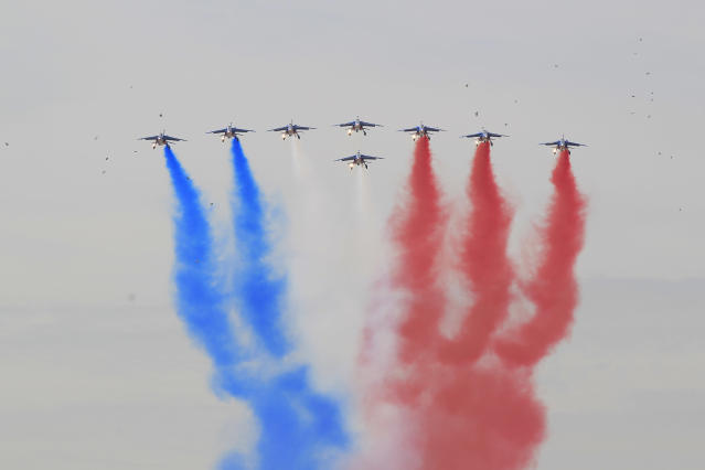Birds fly in the sky as jet fighters of the French Army fly over central court displaying the colors of the French national flag to mark the start of the French Open tennis tournament in Roland Garros stadium in Paris, Sunday May 27, 2012. (AP Photo/Bernat Armangue)