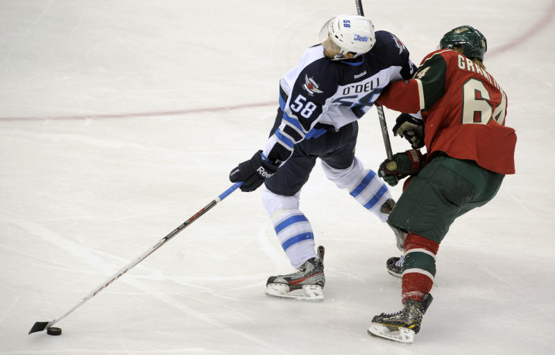 Minnesota Wild's Mikael Granlund, right, gets his stick under the arm of Winnigeg Jets' Eric O'Dell (58) in the second period of an NHL hockey game on Saturday, Sept. 21, 2013, in St. Paul, Minn. Granlund got a penalty for hooking on the play. (AP Photo/Tom Olmscheid)
