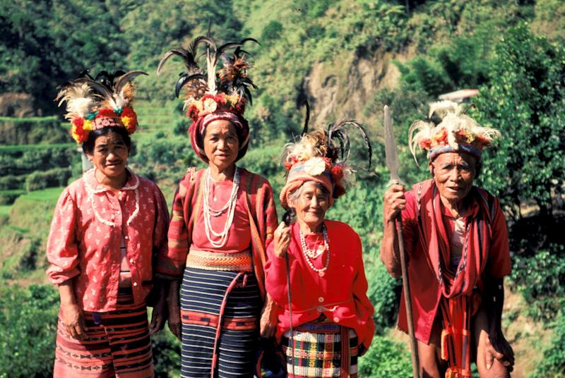 Ifugao women show their traditional costumes as they stand among rice terraces built by their ancestors and maintained bythe tribe.
