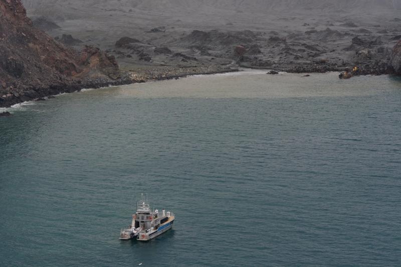A New Zealand Defence boat approaches White Island which is covered in ash.