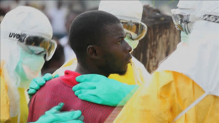 Health workers surround an Ebola patient who escaped from quarantine from Monrovia's Elwa hospital, in the centre of Paynesville in this still image taken from a September 1, 2014 video. REUTERS/Reuters TV