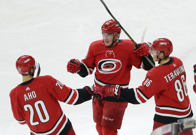 Carolina Hurricanes' Micheal Ferland, center, is congratulated by Sebastian Aho (20) and Teuvo Teravainen (86), both of Finland, following Ferland's goal against the Toronto Maple Leafs during the third period of an NHL hockey game in Raleigh, N.C., Wednesday, Nov. 21, 2018. Carolina won 5-2. (AP Photo/Gerry Broome)
