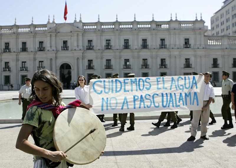 """FILE - In this March 22, 2006 file photo, a woman plays a Kultrum, a traditional Mapuche instrument, during a demonstration on World Water Day by people holding a sign that reads in Spanish """"""""Let us take care the water, No to Pascua Lama"""" rejecting a gold mining project they claim will  affect water supply to a fertile valley in northern Chile, outside the presidential palace La Moneda in Santiago, Chile. A Chilean court halted on April 10, 2013 the construction of Barrick Gold Corp.'s $8 billion, border-straddling mine on the high-altitude spine of the Andes. Barrick also faces growing environmental resistance in Argentina, which shares the Pascua-Lama project, and the Dominican Republic's government is insisting on rewriting the royalties contract for its $4 billion Pueblo Viejo mine. (AP Photo/Santiago Llanquin, File)"""