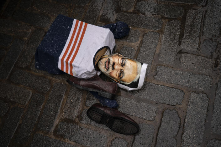 An effigy of Narendra Modi, prime minister of India, lies on the ground as protesters gather outside the Consulate General of India, Tuesday, Jan. 26, 2021, in the Manhattan borough of New York. Tens of thousands of protesting farmers have marched, rode horses and drove long lines of tractors into India's capital, breaking through police barricades to storm the historic Red Fort. The farmers have been demanding the withdrawal of new laws that they say will favor large corporate farms and devastate the earnings of smaller scale farmers. Republic Day marks the anniversary of the adoption of India's constitution on Jan. 26, 1950. (AP Photo/John Minchillo)