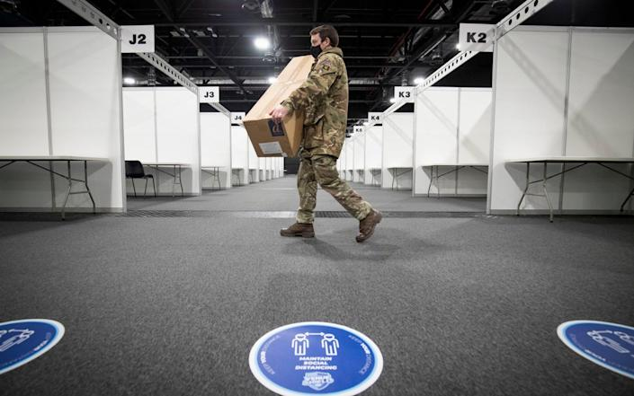 A member of the Royal Scots Dragoon Guard carries in supplies as part of the final preparations setting up a mass Covid vaccination centre - Jane Barlow/PA