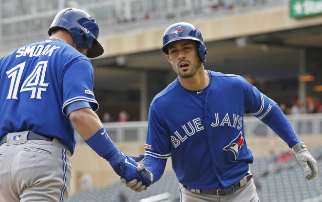 Toronto Blue Jays' Randal Grichuk, right, is congratulated by Justin Smoak after Grichuk's solo home run off Minnesota Twins pitcher Michael Pineda in the first inning of a baseball game Thursday, April 18, 2019, in Minneapolis. (AP Photo/Jim Mone)