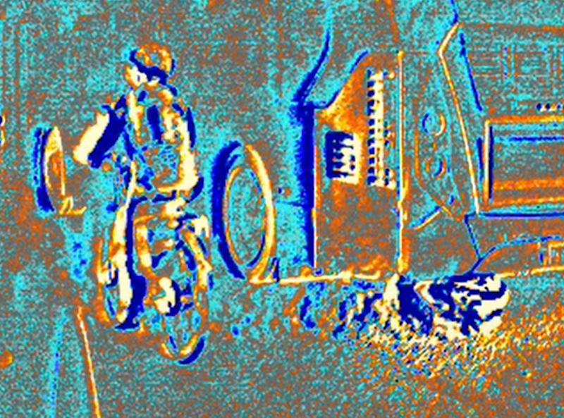 An enhanced view of exhaust fumes from a bus shows them swirling around a cyclist (FLIR Systems)