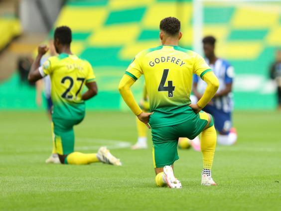 Norwich and Brighton players take a knee at the start of their Premier League match (AP)
