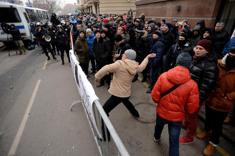 A protester throws a stone towards the Turkish embassy in Moscow on November 25, 2015 (AFP Photo/Kirill Kudryavtsev)