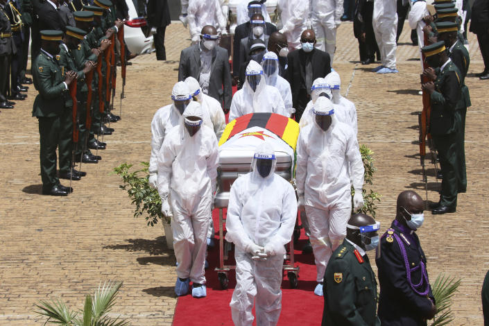 """Pallbearers carry the coffin of government minister Dr Ellen Gwaradzimba who died of COVID-19, in Harare, Thursday, Jan. 21, 2021. Zimbabwean President Emmerson Mnangagwa who presided over the burial called the pandemic """"evil"""" and urged people to wear masks, practice social distancing and sanitize, as cases across the country increased amid a fragile health system. (AP Photo/Tsvangirayi Mukwazhi)"""
