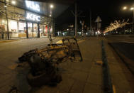 The burned wreck of a motor scooter lays on the pavement outside a fast-food restaurant that had it's windows smashed in protests against a nation-wide curfew in Rotterdam, Netherlands, Monday, Jan. 25, 2021. The Netherlands Saturday entered its toughest phase of anti-coronavirus restrictions to date, imposing a nationwide night-time curfew from 9 p.m. until 4:30 a.m. in a bid to control the COVID-19 infection rate. (AP Photo/Peter Dejong)