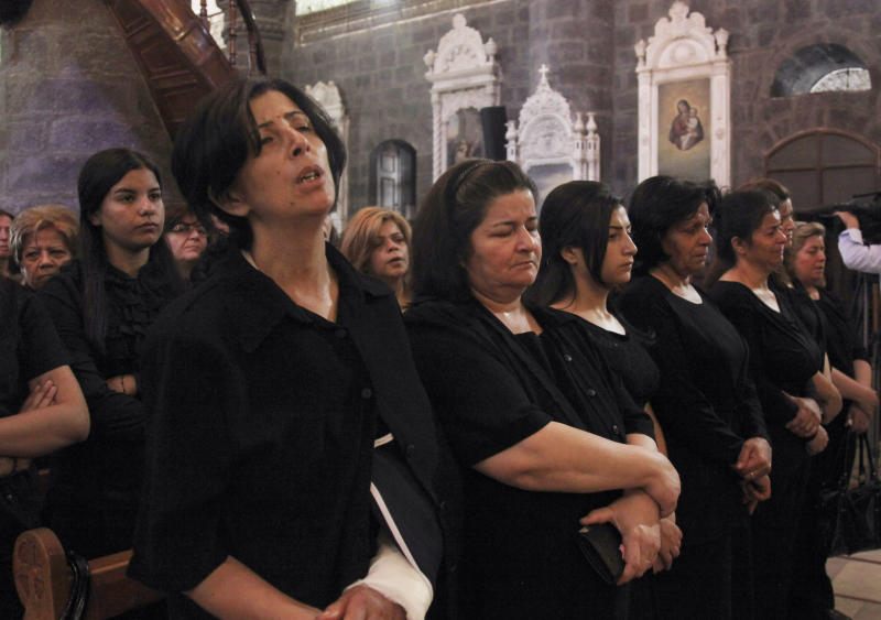Women attend a prayer at al-Zaytoun Roman Catholic Church in Damascus, Syria, Saturday, Sept. 14, 2013. Government troops are battling for the ancient Christian village of Maaloula northeast of the capital of Damascus that was a major tourist attraction before the civil war. (AP Photo)