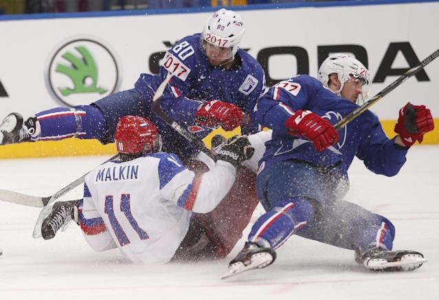 Russia forward Evgeni Malkin, bottom, crashes into France forward Teddy Da Costa, top and France forward Brian Henderson, right, during a quarterfinal match between France and Russia at the Ice Hockey World Championship in Minsk, Belarus, Thursday, May 22, 2014. (AP Photo/Darko Bandic)