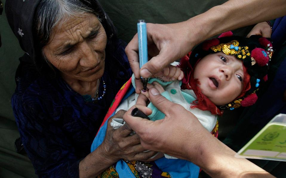 A Pakistani health worker marks an infant after immunisation with anti-polio drops in Lahore, Pakistan - AP
