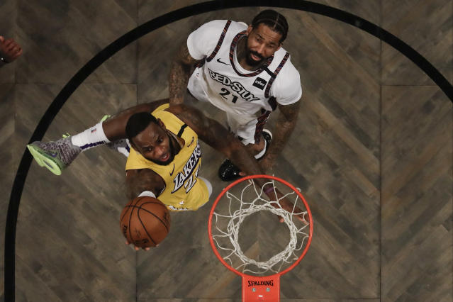 Los Angeles Lakers' LeBron James (23) drives past Brooklyn Nets' Wilson Chandler (21) during the first half of an NBA basketball game Thursday, Jan. 23, 2020, in New York. (AP Photo/Frank Franklin II)