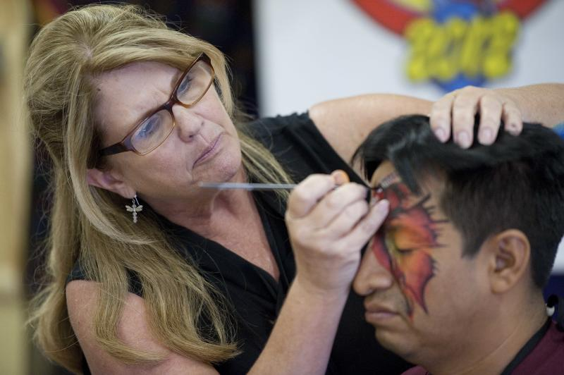 """In a July 31, 2012 photo, Donna Hofstee, aka """"Dizzy Darla"""" the clown, demonstrates face painting techniques on Jose Morales, or """"Cascarita,"""" at the third annual Clown Campin' in Ontario, Calif. The week-long event is held for clowns across the United States and Canada to learn, get inspired, and network. (AP Photo/Grant Hindsley)"""