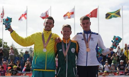Triathlon - Gold Coast 2018 Commonwealth Games - Men's Final - Southport Broadwater Parklands - Gold Coast, Australia - April 5, 2018 - Gold medallist Henri Schoeman of South Africa, silver medallist Jacob Birtwhistle of Australia, bronze medallist Marc Austin of Scotland. REUTERS/Athit Perawongmetha