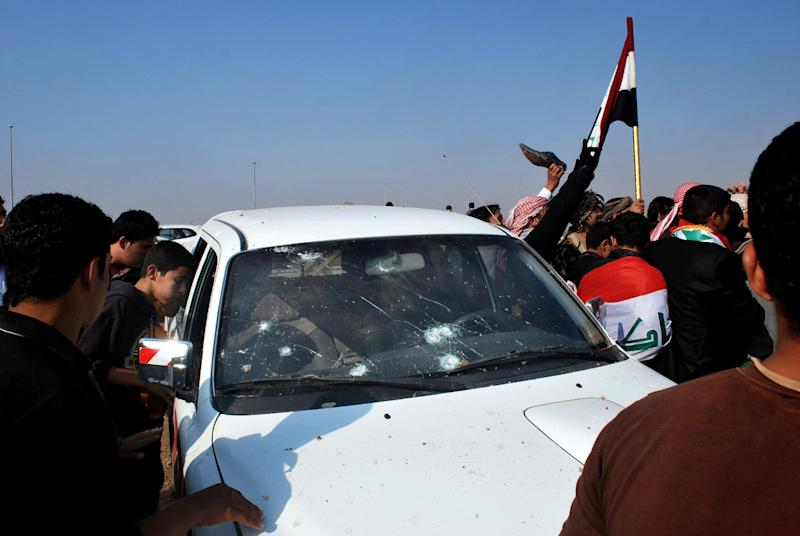 Protesters inspect a damaged vehicle during a demonstrations in Ramadi, 70 miles (115 kilometers) west of Baghdad, Iraq, Sunday, Dec. 30, 2012. Gunshots wounded at least two people Sunday at demonstrations in western Iraq when bodyguards protecting a senior Sunni politician opened fire to disperse protesters, a local official said, marking the first casualties in a week of rallies. (AP Photo)