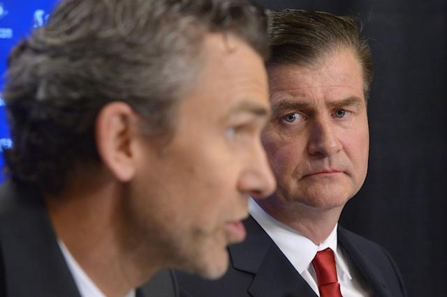Jim Benning, new general manager of the Vancouver Canucks, looks on as president of hockey operations Trevor Linden speaks at a news conference in Vancouver, Friday May 23, 2014. (AP Photo/The Canadian Press, Jonathan Hayward)