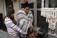 <p>Karla Perez and Esperanza Gonzalez warm up by a barbecue grill during the power outage in Houston, Texas.</p>