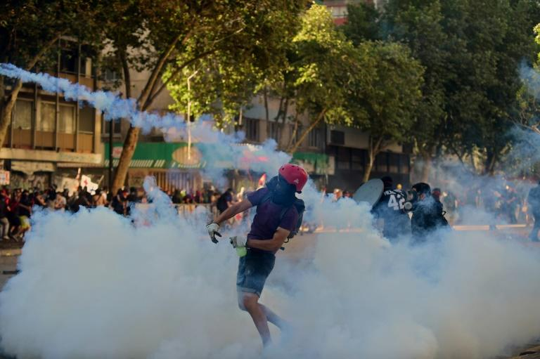 """Chilean demonstrators clash with security forces during a protest against the government in Santiago on November 29, 2019: the Inter-American Commission on Human Rights has called on Chile to end the use  of """"excessive force"""""""
