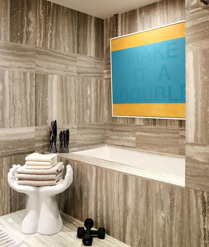 """<p>While dark rooms are cozy, adding vibrant artwork will elevate the mood and look of the space. A bold painting in yellow and turquoise pops against travertine tiles in this <a href=""""https://www.elledecor.com/design-decorate/house-interiors/a31039049/thom-filicia-new-manhattan-apartment/"""" rel=""""nofollow noopener"""" target=""""_blank"""" data-ylk=""""slk:Manhattan apartment"""" class=""""link rapid-noclick-resp"""">Manhattan apartment</a>. </p>"""
