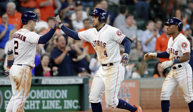 Houston Astros Alex Bregman (2) high fives George Springer (4) after scoring on his two run home run, driving in Tony Kemp (18) during the fifth inning of a baseball game against the San Francisco Giants Wednesday, May 23, 2018, in Houston. (AP Photo/Michael Wyke)