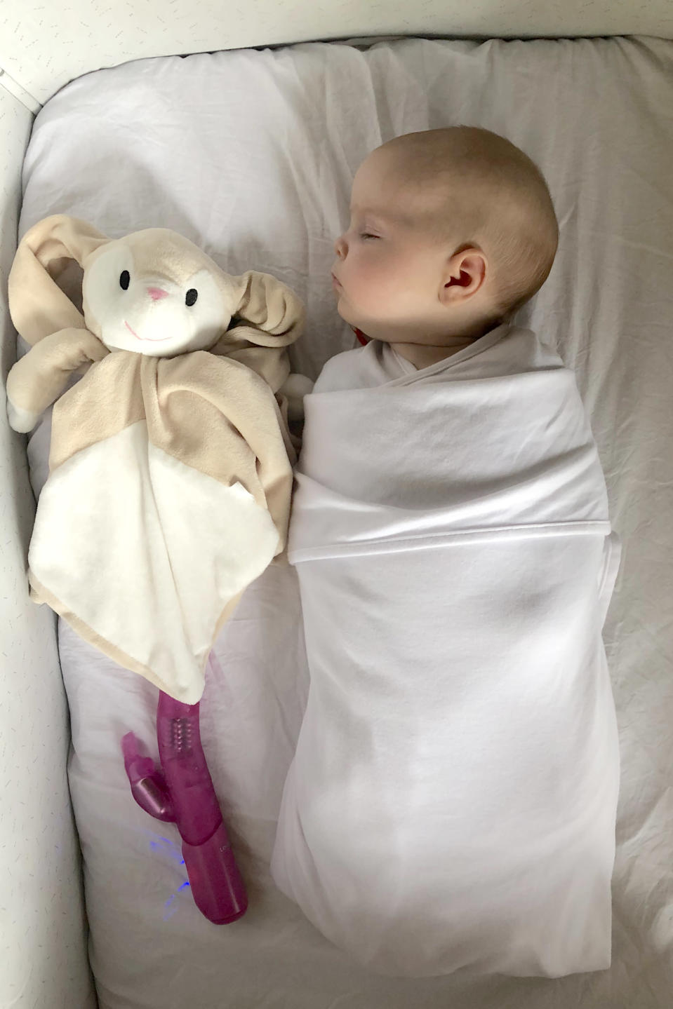 Baby Lucie fast asleep with the vibrator [Photo: Caters News Agency]