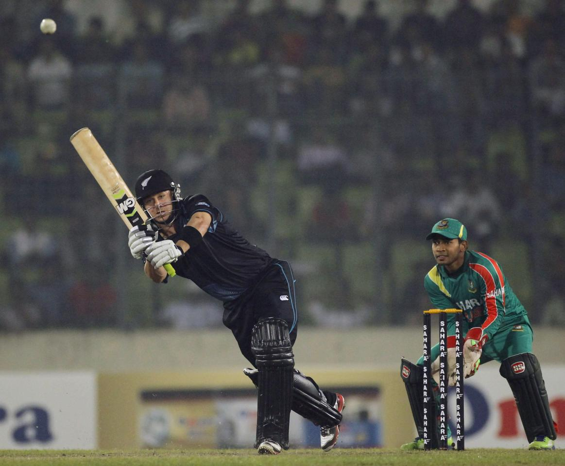New Zealand's Nathan McCullum plays a shot as Bangladesh's Mushfiqur Rahim (R) watches during their second one-day international (ODI) cricket match in Dhaka October 31, 2013. REUTERS/Andrew Biraj (BANGLADESH - Tags: SPORT CRICKET)