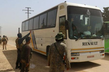Rebel fighters welcome a convoy of buses carrying Sunni rebels and civilians, who were evacuated from Zabadani and Madaya, as part of a reciprocal evacuation deal for four besieged towns, upon their arrival at al-Rashideen