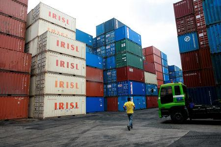 FILE PHOTO: A truck driver walks past a stack of IRISL containers at a depot in northern Singapore February 4, 2012. REUTERS/Thomas White/File Photo