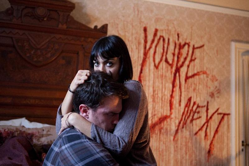 """This film publicity image released by Lionsgate shows Nick Tucci and Wendy Glenn, right, in a scene from """"You're Next."""" (AP Photo/Lionsgate, Corey Ransberg)"""