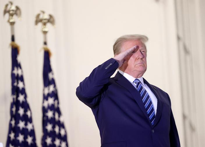 U.S. President Donald Trump salutes Marine One helicopter pilots after returning to the White House from Walter Reed National Military Medical Center on October 05, 2020 in Washington, DC. Trump spent three days hospitalized for coronavirus. (Win McNamee/Getty Images)