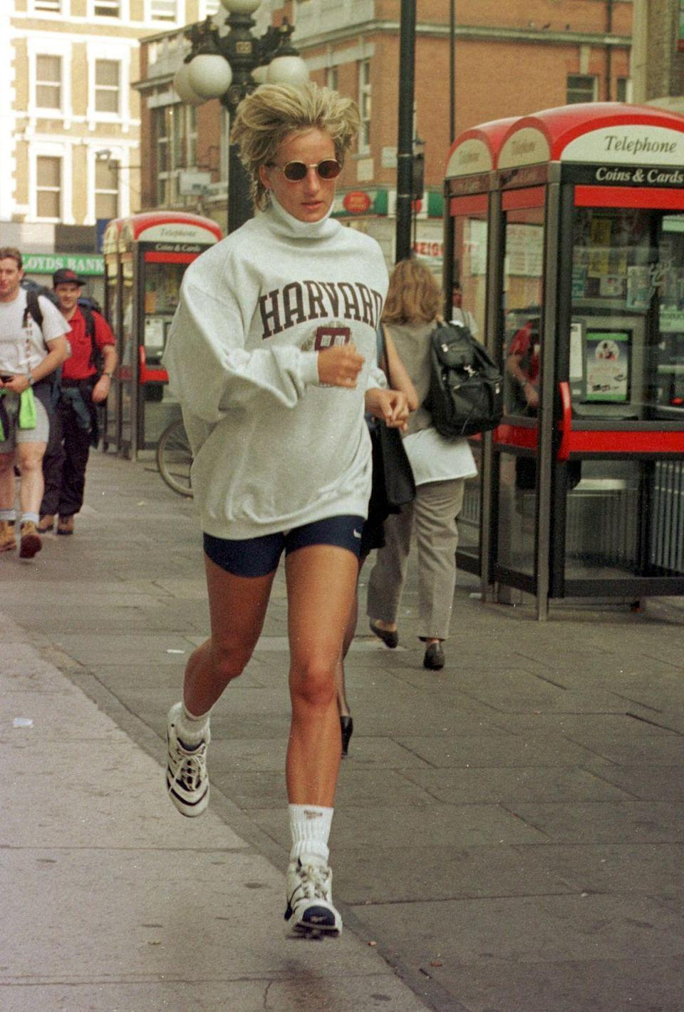 """<p>This is perhaps the most famous of the """"Diana outfits."""" The Princess rewore her Harvard sweatshirt multiple times, usually paired with black spandex shorts and small circular glasses. </p>"""
