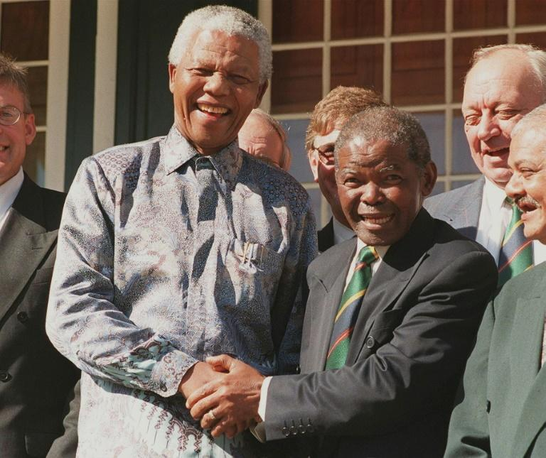 President Nelson Mandela (L) greets SA Rugby president Silas Nkanunu during a 1998 meeting in Cape Town