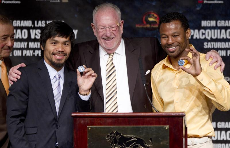Las Vegas Mayor Oscar Goodman, center, poses for photos with Manny Pacquiao, left, and Shane Mosley after presenting them with chips to the city before the start of a boxing news conference, Wednesday, May 4, 2011, in Las Vegas. Pacquiao will defend his WBO welterweight title against Mosley on Saturday. (AP Photo/Julie Jacobson)