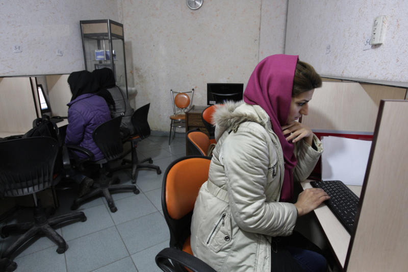 FILE - In this Monday, Feb. 13, 2012 file photo, Iranian women use computers at an Internet cafe in central Tehran. Iran's cyber monitors often tout their efforts to fight the West's 'soft war' of influence through the web, but trying to ban Google's popular Gmail may have gone too far with complaints coming even from email-starved parliament members. (AP Photo/Vahid Salemi, File)