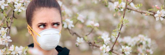 White woman with brown hair in a bun wearing a face mask and standing among white flowering trees