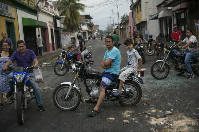 Residents assess the damage a day after clashes between Bolivarian National Guards and anti-government protesters in Urena, Venezuela, near the border with Colombia, Sunday, Feb. 24, 2019. A U.S.-backed drive to deliver foreign aid to Venezuela on Saturday met strong resistance as Venezuelan troops loyal to President Nicolas Maduro blocked the convoys at the border and fired tear gas on protesters. (AP Photo/Rodrigo Abd)