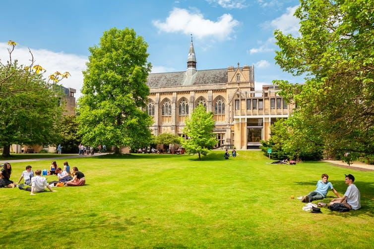 Students sitting on grass outside Balliol College, Oxford.