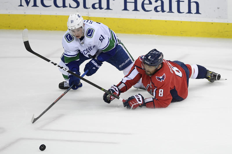 Washington Capitals left wing Alex Ovechkin (8), of Russia, battles for the puck against Vancouver Canucks defenseman Troy Stecher (51) during the third period of an NHL hockey game, Tuesday, Feb. 5, 2019, in Washington. The Capitals won 3-2. (AP Photo/Nick Wass)