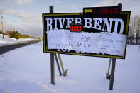 """FILE - A """"closed"""" sign is posted at the River Bend Smelt Camps, Wednesday, Feb. 10, 2021, in Bowdoinham, Maine. The late arriving cold weather has been a blow to some ice fishing businesses. (AP Photo/Robert F. Bukaty)"""