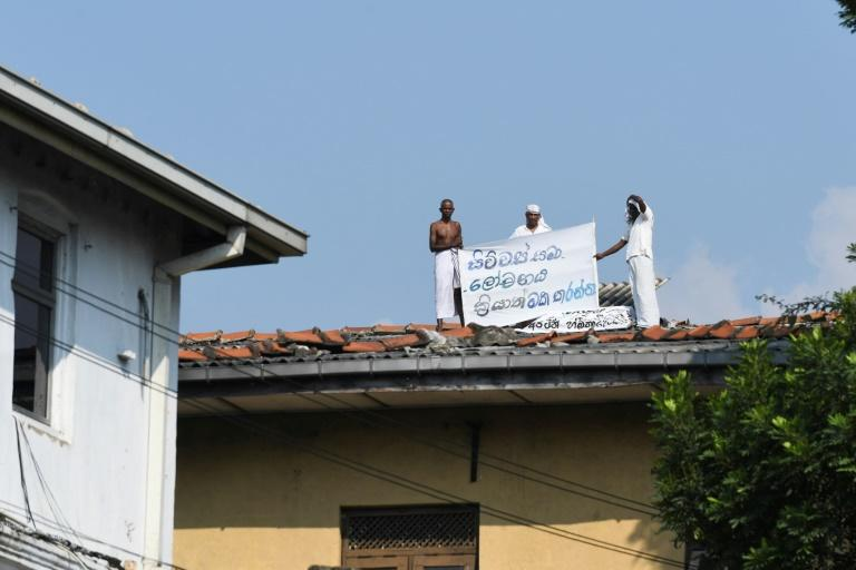 Inmates on the roof of Welikada prison in Sri Lanka display a banner calling for a pardon similar to that granted the murderer of a Swedish teen at the weekend (AFP Photo/Lakruwan WANNIARACHCHI)