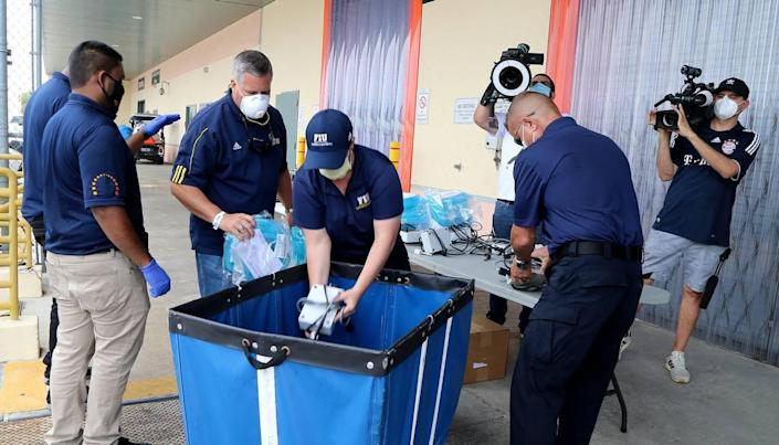 FIU staff members Javier Marquez (second from left), vice president and chief of staff, and Bridget Pelaez (center), FIU assistant director, emergency, load a set of ventilators that Florida International University is lending to the state to treat patients affected by the COVID-19 outbreak, on Wednesday, April 8, 2020.