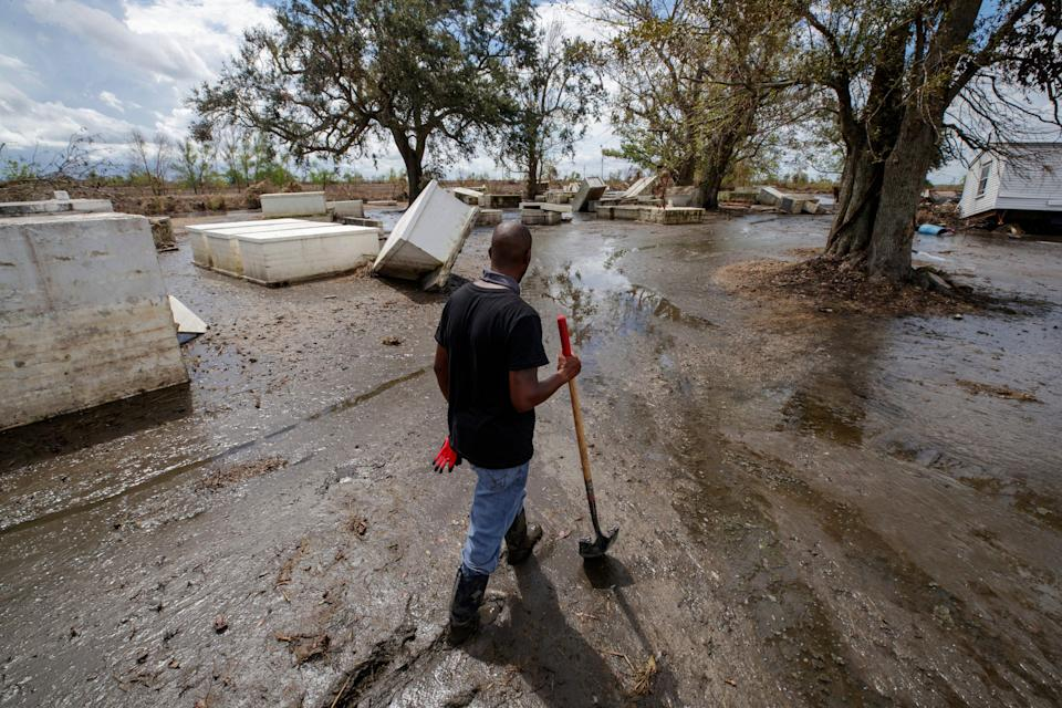 Ironton resident Kornell Davis walks through the Ironton cemetery, still covered in nearly a foot a marsh mud Sunday, Sept. 19, 2021, three weeks after the wind and storm surge from Hurricane Ida devastated the historic African community in Plaquemines Parish, La.
